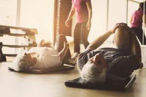 In Motion: Elderly man and woman stretching on mats