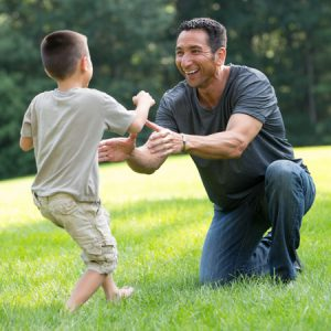 father and son playing outdoors in grass