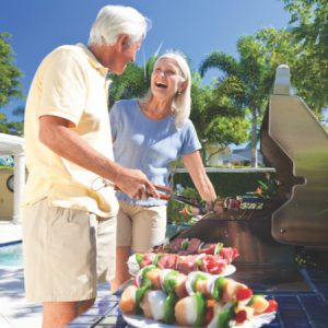 elderly couple grilling